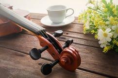 Feche acima do violino no copo de madeira da tabela e de café Imagem de Stock