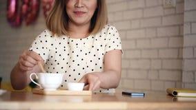 Feche acima do wonman usando a tabuleta no café do café na tabela filme