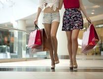Feche acima, dois pares de pés fêmeas com os sacos de compras em seu h Fotografia de Stock Royalty Free
