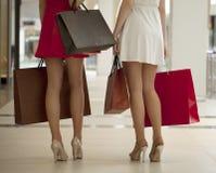 Feche acima, dois pares de pés fêmeas com os sacos de compras em seu h Fotos de Stock Royalty Free
