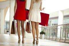 Feche acima, dois pares de pés fêmeas com os sacos de compras em seu h Imagem de Stock Royalty Free