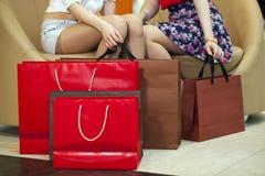 Feche acima, dois pares de pés fêmeas com sacos de compras Imagens de Stock Royalty Free