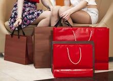 Feche acima, dois pares de pés fêmeas com sacos de compras Imagens de Stock