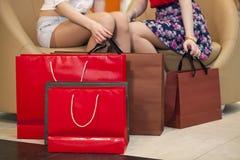 Feche acima, dois pares de pés fêmeas com sacos de compras Fotografia de Stock
