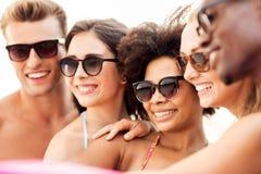 Feche acima dos amigos felizes nos óculos de sol no verão fotografia de stock