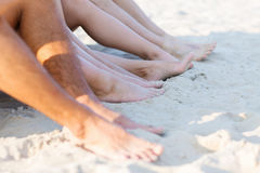 Feche acima dos amigos que sentam-se na praia do verão Foto de Stock