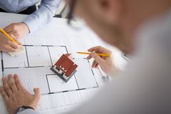 Feche acima dos arquitetos que discutem o projeto da casa imagem de stock