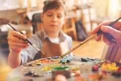 Feche acima dos artistas novos que misturam pinturas na paleta Imagens de Stock Royalty Free