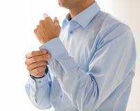 Feche acima dos botões da asseguração do homem na luva da camisa imagens de stock