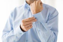 Feche acima dos botões da asseguração do homem na luva da camisa fotografia de stock