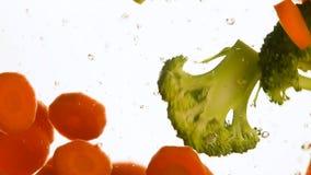 Feche acima dos brócolis e do flutuador jogado cenoura na água filme