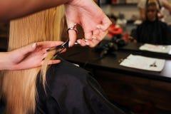 Feche acima dos cabeleireiro entregam o corte do cabelo louro Fazendo o corte de cabelo novo no salão de beleza imagens de stock