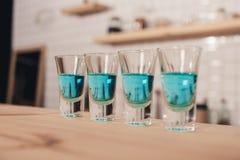 feche acima dos cocktail azuis nos vidros de tiro que estão no contador da barra Imagem de Stock