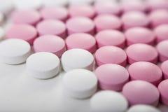 Feche acima dos comprimidos cor-de-rosa e brancos Imagem de Stock