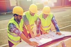 Feche acima dos construtores com o modelo na capa do carro Fotografia de Stock Royalty Free