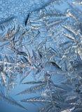 Feche acima dos cristais de gelo contra o fundo azul Fotografia de Stock Royalty Free