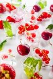 Feche acima dos cubos de gelo com as bagas frescas entre as folhas não congeladas da cereja, da morango e da hortelã no fundo bra Imagem de Stock