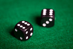 Feche acima dos dados pretos na tabela verde do casino Imagem de Stock