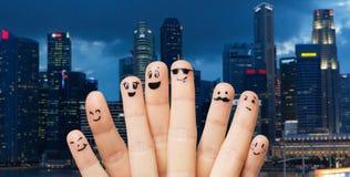 Feche acima dos dedos com as caras do smiley sobre a cidade Imagens de Stock