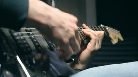 Feche acima dos dedos do guitarrista nas cordas Solo dos jogos dos braços dos homens da música rock Mãos do músico masculino que  vídeos de arquivo