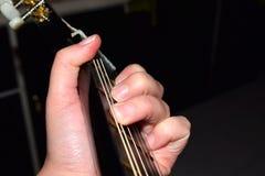 Feche acima dos dedos que jogam a guitarra clássica Músico que executa músicas imagem de stock royalty free