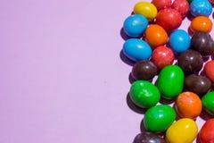 Feche acima dos doces redondos coloridos no fundo cor-de-rosa Foto de Stock Royalty Free