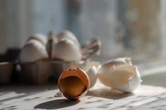 Feche acima dos escudos de ovo quebrados no fundo de madeira imagem de stock