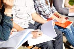Feche acima dos estudantes com os cadernos no terreno Imagens de Stock