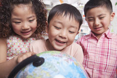 Feche acima dos estudantes que olham um globo Fotografia de Stock
