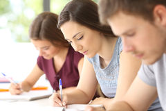 Feche acima dos estudantes sérios que tomam notas Fotografia de Stock