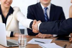 Feche acima dos executivos que agitam as mãos na reunião ou na negociação no escritório Os sócios são satisfeitos porque Imagens de Stock