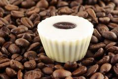 Feche acima dos feijões de café e dos bombons um Fotografia de Stock