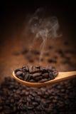 Feche acima dos feijões de café na colher de madeira Fotos de Stock Royalty Free