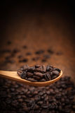 Feche acima dos feijões de café na colher de madeira Foto de Stock Royalty Free