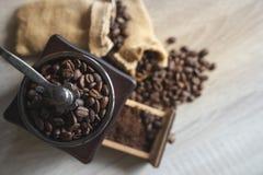 Feche acima dos feijões de café Roasted da vista superior no moedor de café de madeira Imagens de Stock Royalty Free