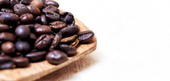 Feche acima dos feijões de café roasted em uma colher de madeira com parte traseira do branco Imagem de Stock Royalty Free