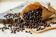 Feche acima dos feijões de café roasted em uns sacos de papel no fundo de madeira Foto de Stock