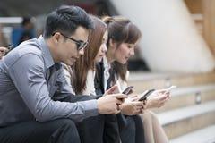 Feche acima dos homens de negócios e das mulheres de negócios que usam o smartphone Imagens de Stock