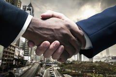 Feche acima dos homens de negócios que agitam as mãos com arquitectura da cidade no fundo Imagem de Stock Royalty Free