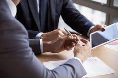 Feche acima dos homens de negócios usando a tabuleta de Digitas na reunião foto de stock royalty free