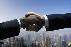 Feche acima dos homens de negócios que agitam as mãos com arquitectura da cidade no fundo Fotografia de Stock Royalty Free