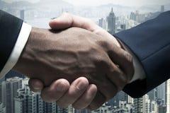 Feche acima dos homens de negócios que agitam as mãos com arquitectura da cidade no fundo Imagens de Stock Royalty Free