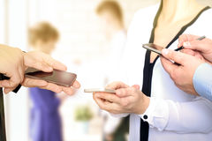 Feche acima dos homens e da mulher de negócio que usa telefones espertos móveis Fotos de Stock Royalty Free