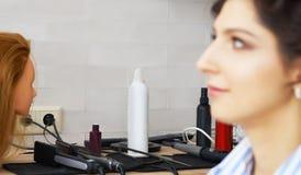 Feche acima dos instrumentos profissionais do hairdstyle com a cara modelo no primeiro plano fora de foco fotografia de stock