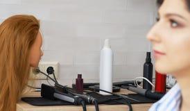 Feche acima dos instrumentos profissionais do hairdstyle com a cara modelo no primeiro plano fora de foco foto de stock
