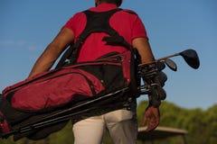 Feche acima dos jogadores de golfe para trás ao andar e ao levar o saco de golfe foto de stock