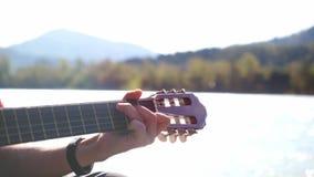 Feche acima dos jogos da mão do ` s do indivíduo em uma guitarra que senta-se pelo rio da montanha no dia ensolarado no movimento filme