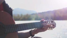 Feche acima dos jogos do indivíduo da mão em uma guitarra que senta-se pelo rio da montanha no dia ensolarado no movimento lento  vídeos de arquivo
