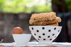 Feche acima dos macarronetes imediatos na bacia com ovo imagem de stock