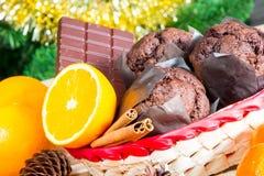 Feche acima dos maffins, das laranjas e do chocolate no fundo da árvore de Natal Imagens de Stock Royalty Free
